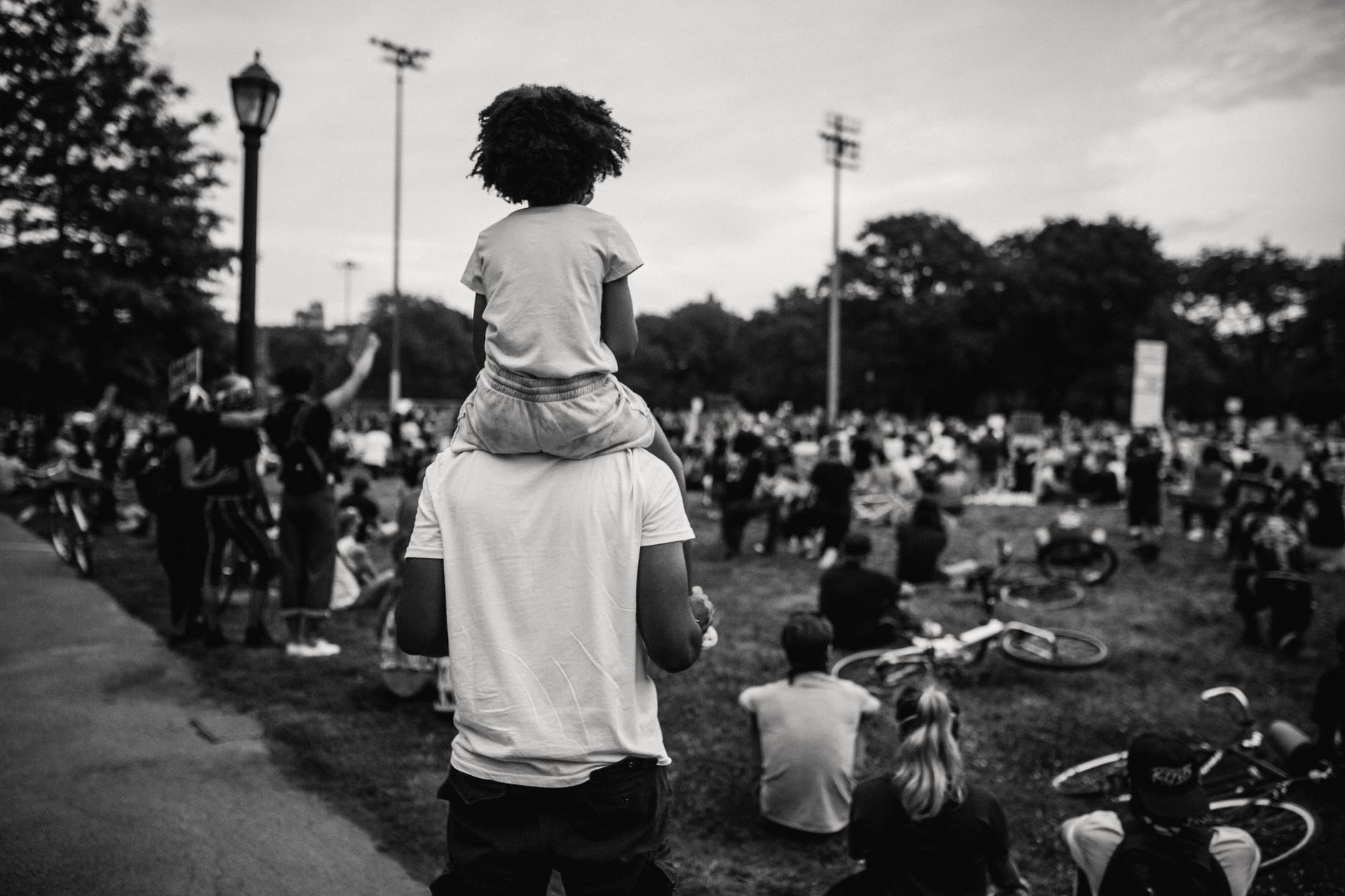 person with a child on his shoulders looking at a protest